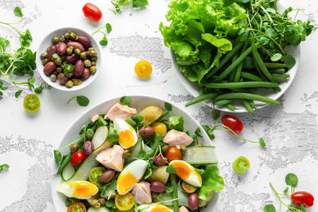 Healthy Nicoise salad with salmon, colourful sweet cherry tomatoes, olives, green beans, cucumber ribbons, soft boiled eggs, water-cress leaves with Mediterranean seasoning.