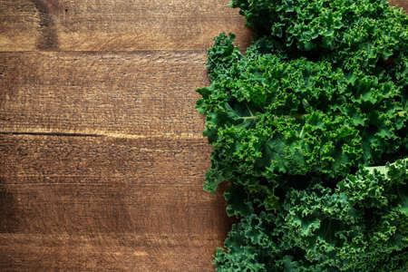Raw organic freshly picked green curly kale on wooden table.