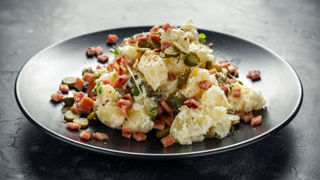 Warm potato salad with gherkins, bacon in a black plate. Stockfoto