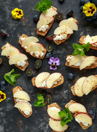 Healthy breakfast toasts with cottage cheese and nectarine slices, sprinkled with cinnamon, served with dark grapes and edible flowers.