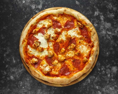 Hausgemachte rustikale Pizza mit Salami und Hühnchen mit geschmolzenem Mozzarella.