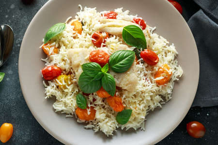 Steamed cod fish with rice and cherry mix tomatoes and basil herbs in a plate. 스톡 콘텐츠