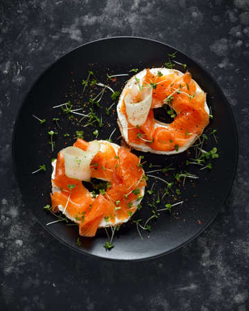 Smoked salmon bagel toasts with soft cheese, cucumber ribbons and cress salad Stock Photo