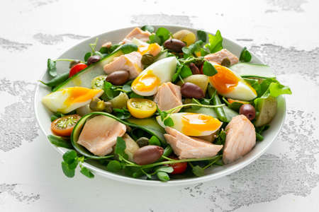 Healthy Nicoise salad with salmon, colourful sweet cherry tomatoes, olives, green beans, cucumber ribbons, soft boiled eggs, water-cress leaves with Mediterranean seasoning