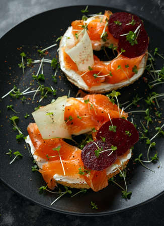 Smoked salmon bagel toasts with soft cheese, cucumber ribbons and beetroot and dill, cress salad Stock Photo