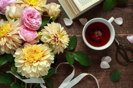 Summer theme tea with freshly picked flower bouquet: dahlias and roses on wooden table. Rustic style Archivio Fotografico - 106340689