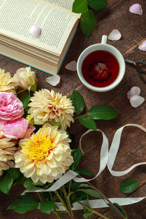 Summer theme tea with freshly picked flower bouquet: dahlias and roses on wooden table. Rustic style Archivio Fotografico - 106340690