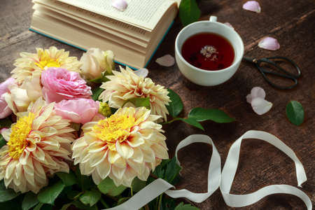 Summer theme tea with freshly picked flower bouquet: dahlias and roses on wooden table. Rustic style