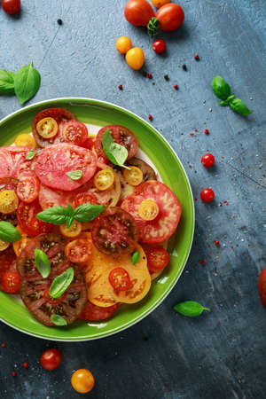 Colorful Tomato Salad with heirloom, pear shaped, beef heart, tigerella, brandywine, cherry, black tomatoes in a green plate. healthy food Reklamní fotografie
