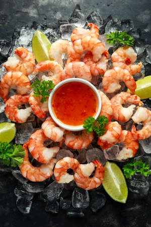 Tiger shrimps served on ice with lime wedges and sweet chilli dip