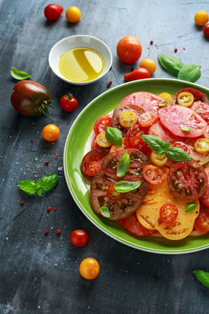 Colorful Tomato Salad with heirloom, pear shaped, beef heart, tigerella, brandywine, cherry, black tomatoes in a green plate. healthy food.