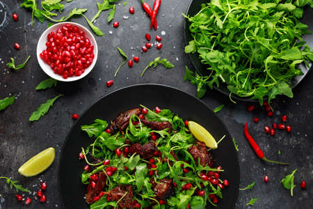 Spicy crispy duck salad with pomegranate seeds, lime and wild green rucola Reklamní fotografie