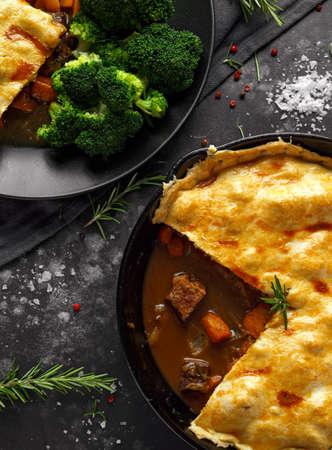 Traditional English beef beer, ale pie served with carrots and broccoli