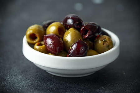 Black, Green Olives with herbs in white bowls