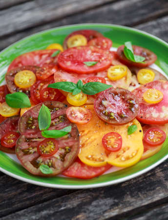 Colorful Tomato Salad with heirloom, pear shaped, beef heart, tigerella, brandywine, cherry, black tomatoes in a green plate. healthy food 写真素材