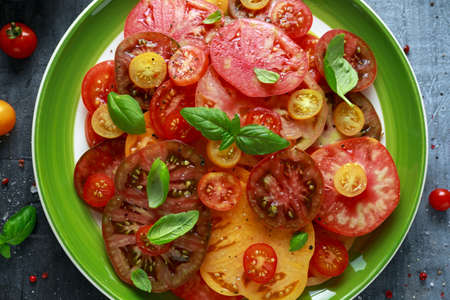 Colorful Tomato Salad with heirloom, pear shaped, beef heart, tigerella, brandywine, cherry, black tomatoes in a green plate. healthy food Banco de Imagens