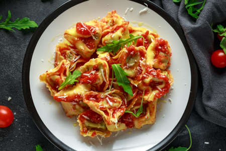 Spinach ricotta Ravioli in tomato sauce with wild rocket and parmesan cheese