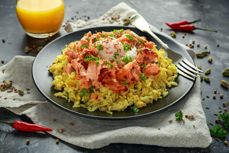 Traditional Indian-English kedgeree breakfast: basmati rice with egg benedict and hot smoked sweet chilli salmon. Stockfoto