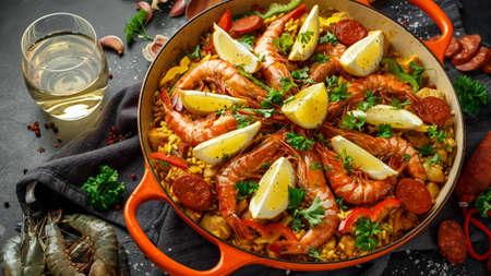 Paella traditionnelle dans la poêle avec poulet, crevettes, chorizo épicé, citron et verre de vin blanc.