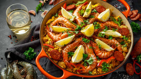 Traditional paella in the fry pan with chicken, prawns, spicy chorizo, lemon and glass of white wine.