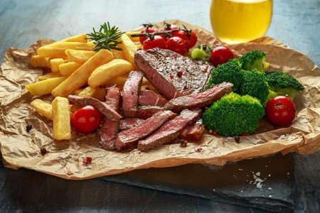 Solomillo a la plancha con patatas fritas, brócoli, cerveza y tomates cherry sobre papel arrugado