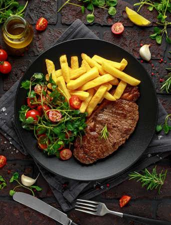 Solomillo a la plancha con patatas fritas y verduras, ensalada de tomate en un plato negro. mesa rústica