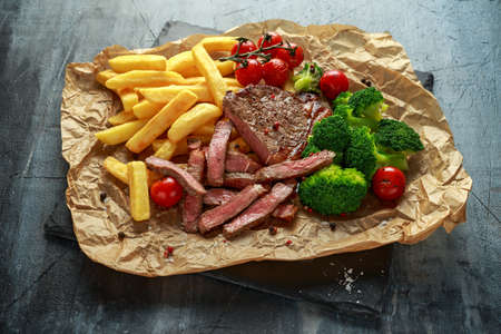 Grilled sirloin steak with potato fries, broccoli and cherry tomatoes on crumpled paper