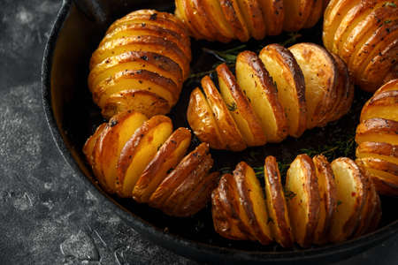 Hasselback baked potatoes served in cast-iron pan with salt, pepper and herbs Foto de archivo