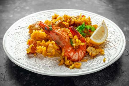 Paella traditionnelle sur plaque blanche avec poulet, crevettes, chorizo épicé, citron et verre de vin blanc.