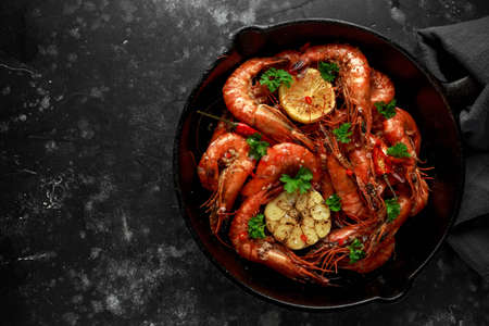 Tiger prawns fried in butter with, lemon juice, garlic and white wine served in cast iron skillet with parsley Archivio Fotografico - 108312594
