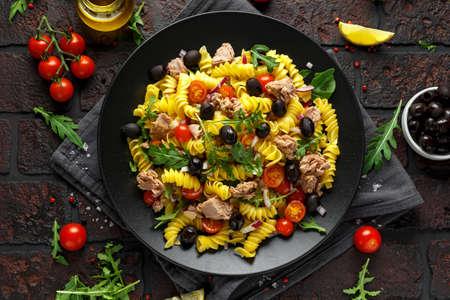 Nudel-Thunfisch-Salat mit Tomaten, wilder Rucola, schwarzen Oliven und roten Zwiebeln