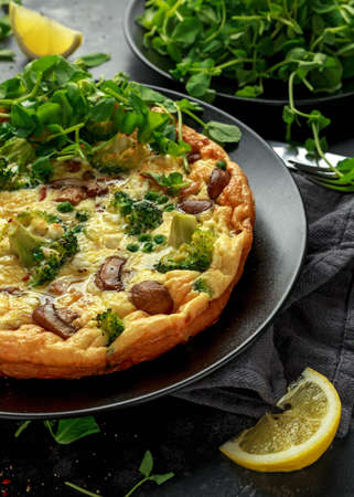 Homemade Frittata with mushrooms, broccoli, feta cheese, green peas and bacon on black plate