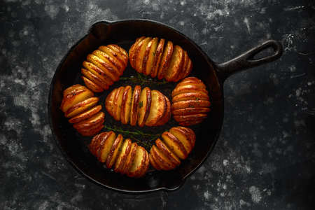 Hasselback baked potatoes served in cast-iron pan with salt, pepper and herbs Reklamní fotografie
