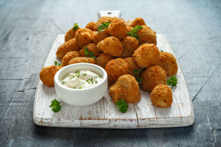 Homemade Breaded Garlic Mushrooms with sour cream and parsley on white wooden board Stock Photo