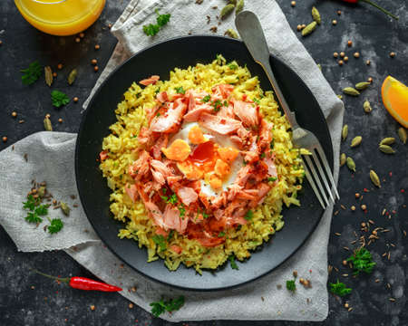 Traditional Indian-English kedgeree breakfast: basmati rice with egg benedict and hot smoked sweet chilli salmon. Stock Photo
