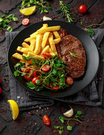 Grilled sirloin steak with potato fries and vegetables, tomato salad in a black plate. rustic table Stock Photo