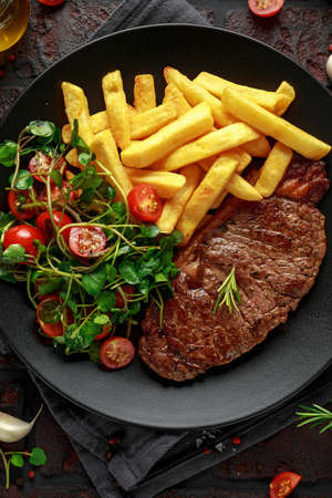 Grilled sirloin steak with potato fries and vegetables, tomato salad in a black plate. rustic table Foto de archivo