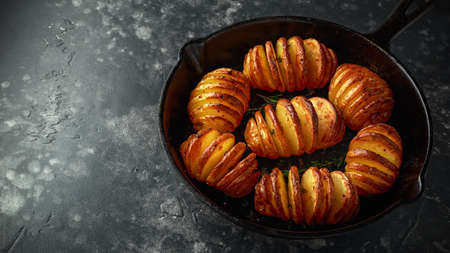 Hasselback baked potatoes served in cast-iron pan with salt, pepper and herbs Stock Photo