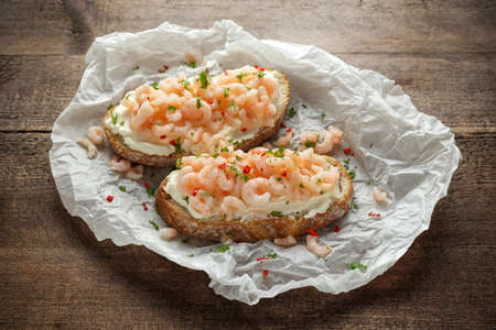 Prawns, shrimp seafood bruschetta with creamy cheese, parsley and chili Stock Photo