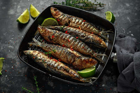 Grilled sardines with thyme, chili and lime wedges on cast iron skillet