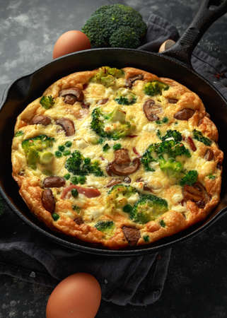 Homemade Frittata with mushrooms, broccoli, feta cheese, green peas and bacon on cast iron skillet Archivio Fotografico