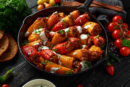 Sausage meat, mince and rice Stuffed sweet mini bell peppers baked in cast iron skillet, pan topped with yogurt and fresh parsley Banco de Imagens