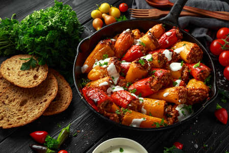 Sausage meat, mince and rice Stuffed sweet mini bell peppers baked in cast iron skillet, pan topped with yogurt and fresh parsley 스톡 콘텐츠