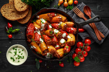 Sausage meat, mince and rice Stuffed sweet mini bell peppers baked in cast iron skillet, pan topped with yogurt and fresh parsley Stock Photo