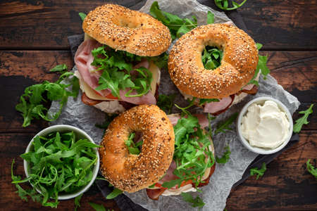 Fresh Bagels Sandwiches with cream cheese, bacon, tomato and green wild rocket on rustic wooden table 스톡 콘텐츠 - 108801556