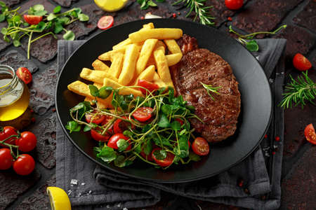 Grilled sirloin steak with potato fries and vegetables, tomato salad in a black plate. rustic table Banco de Imagens
