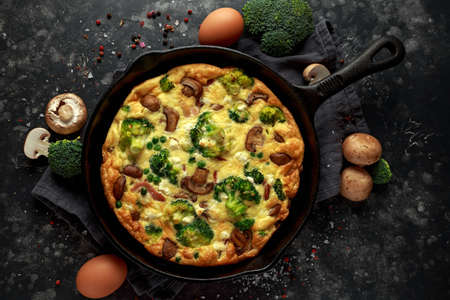 Homemade Frittata with mushrooms, broccoli, feta cheese, green peas and bacon on cast iron skillet Stock Photo