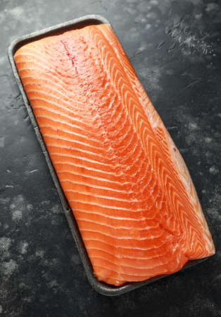 Raw salmon fillet in tray on dark stone background