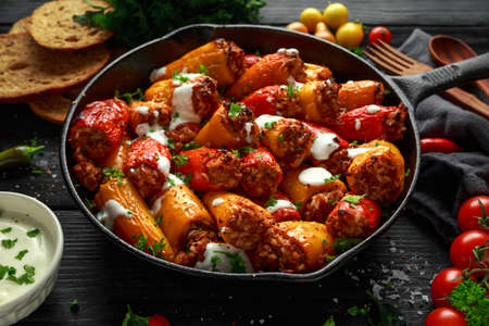 Sausage meat, mince and rice Stuffed sweet mini bell peppers baked in cast iron skillet, pan topped with yogurt and fresh parsley Stok Fotoğraf