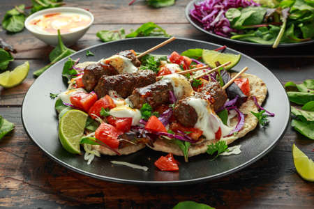 Lamb mint kebabs with flatbread, mix of vegetables, lime and greek yoghurt chilli sauce Stock Photo